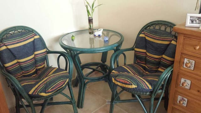 Mesa de mimbre con cristal con sillas a juego con cojines.
