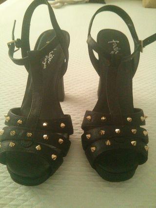Sandalias negras con tachuelas doradas.