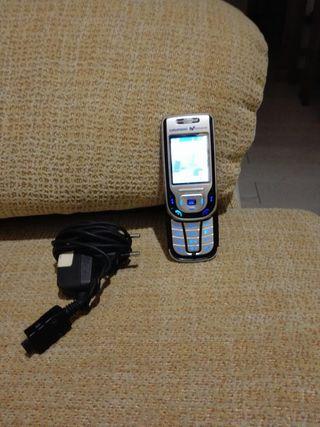 Teléfono móvil con su cargador de Movistar en vent