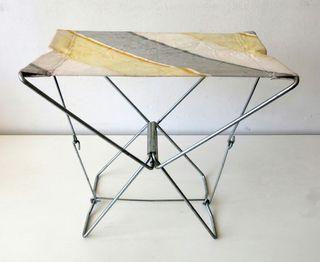 Antiguo taburete plegable, de metal y lona a rayas