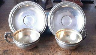 Pareja de tazas con sus platos en plata.