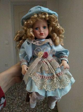 Muñeca de porcelana con silla de madera