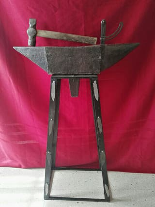 yunke de fragua con mueble de hierro y martillo