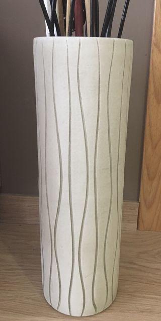 Jarrón de cerámica y cañas decorativas