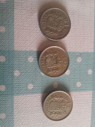 Tres monedas de diez pesetas.