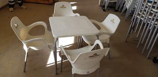 Mesa con 4 sillas a estrenar de plastico blancas