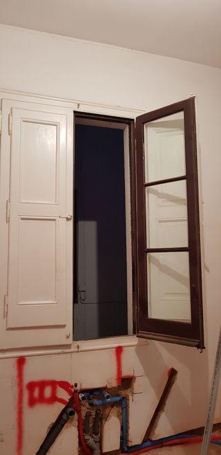ventana antigüa con cristales y porticones