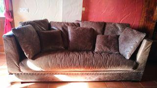 sofa de cuero marrón con remalches y cojines