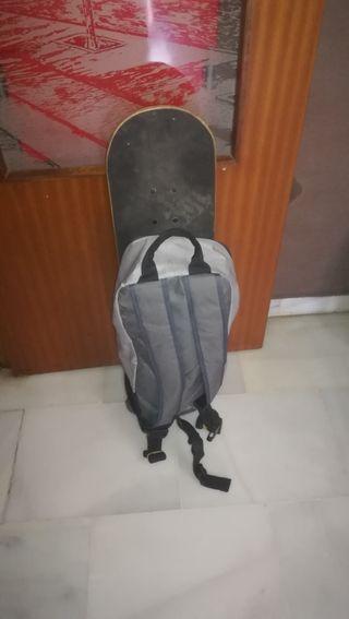 Monopatín con mochila de transporte y protecciones