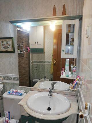 Mueble, grifo, lavabo y espejo de baño.