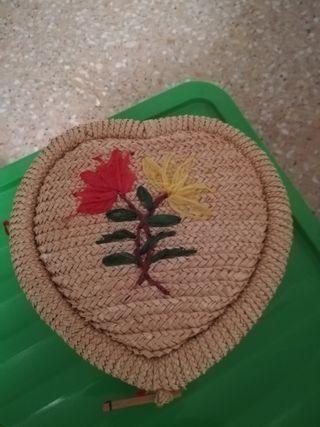 costurero de mimbre forrado de tela de raso roja.
