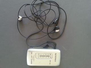 Radio de bolsillo con sus auriculares.