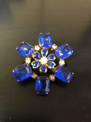 Broche azul turquesa con forma de flor.