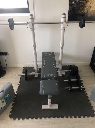 Banco de musculación reclinable con barras y pesas