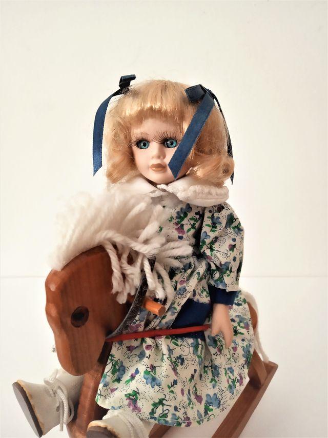 Bonita muñeca de porcelana con caballito de madera