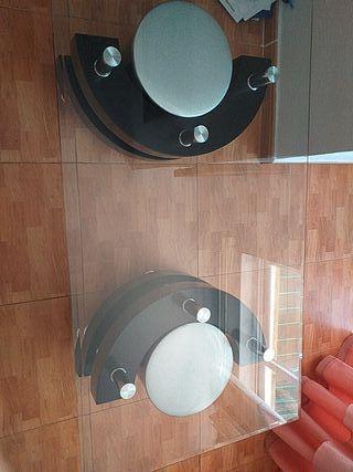 Mesa de cristal con dos taburetes.