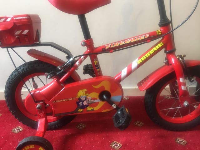 Child's red fire chief bicycle.