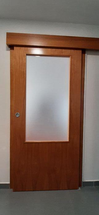 Puerta corredera de madera color cerezo.
