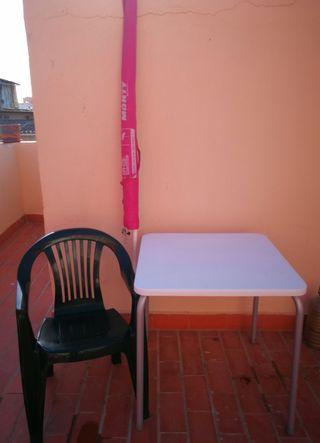 Mesa con silla y sombrilla.
