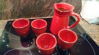 Jarra y 4 tazas de loza, de color rojo