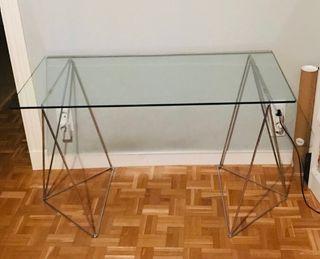 Mesa cristal con caballetes de metal.
