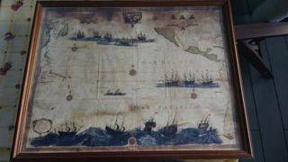 Mapa antiguo y veleros enmarcados.