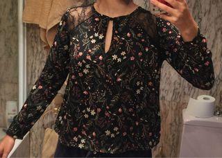 Blusa negra con estampado de flores y encaje negro