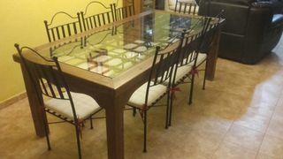 Mesa de forja y muebles de madera rústicos.