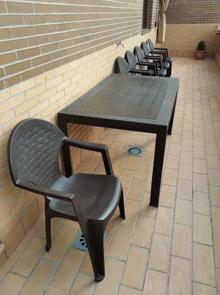 Mesa y sillas de jardín de exterior.