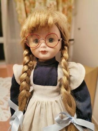 Muñeca de porcelana con trenzas y gafas.
