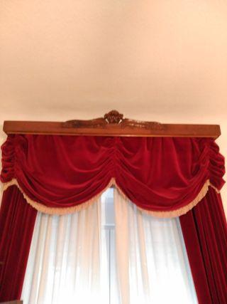 Galería tallada y cortinas de terciopelo