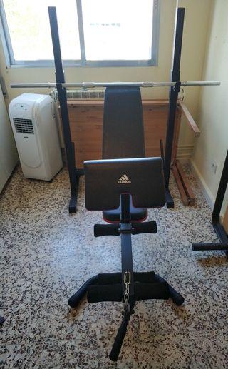 Banco de musculación con barra y pesas