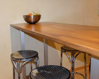 Mesa salón tipo barra con taburetes metálicos