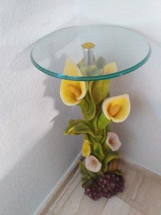 mesa redonda de cristal con pata decorada con flor