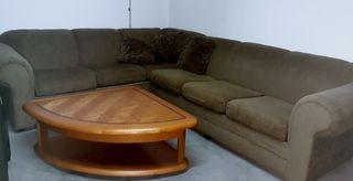 Un sofá cama con una mesa treangular