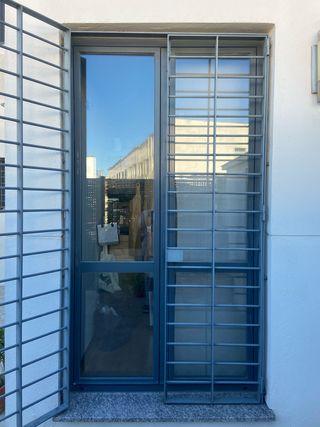 Puerta dos hojas aluminio y cristal INCLUYE REJA