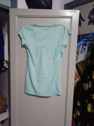 Camisa azul claro con corazón rosa.