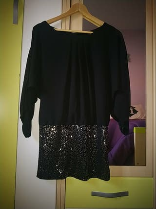vestido negro con lentejuelas en la falda.