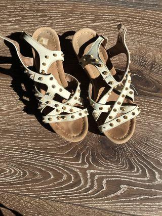 Sandalias de piel blancas con tachuelas doradas
