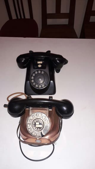 dos telefonos antiguos baquelita negro y cobre.