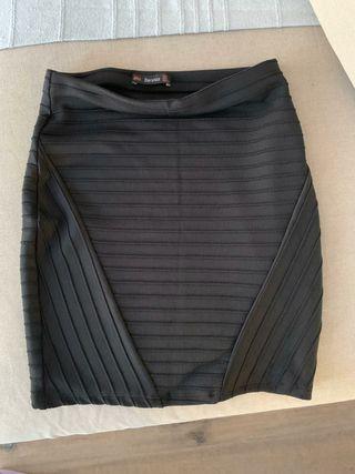 Falda negra ajustada por encima de la rodilla. T S