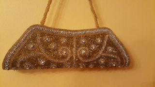 Glamuroso bolso dorado con abalorios.