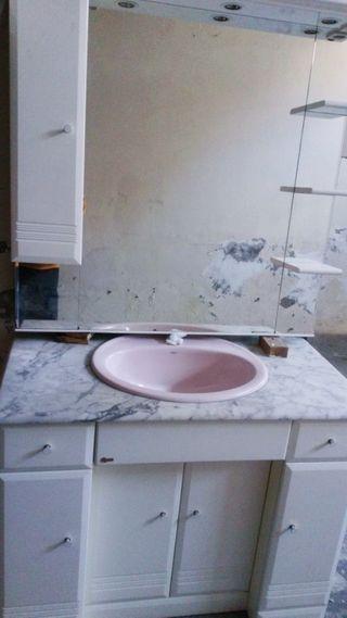 Mueble de baño con espejo y lavabo.