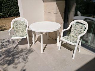 Mesa redonda de jardín y dos sillones.