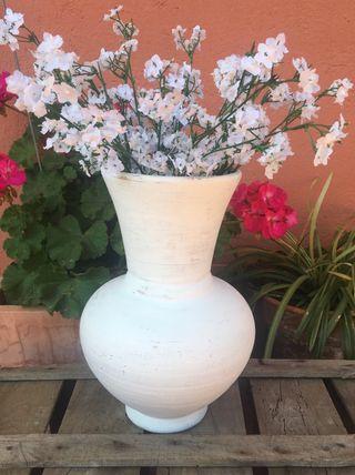 Antiguo jarrón de cerámica con flor artificial