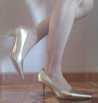 Zapatos de tacón color dorado.