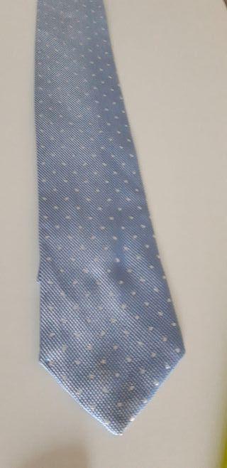 Corbata azul con puntos blancos.