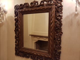 Elegante espejo de marco muy labrado