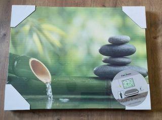 Cuadro con bambú, piedras y agua.