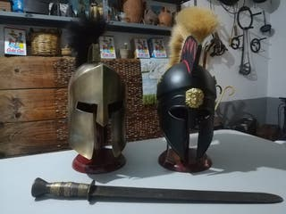 Réplicas de cascos griegos y espada de atrezzo